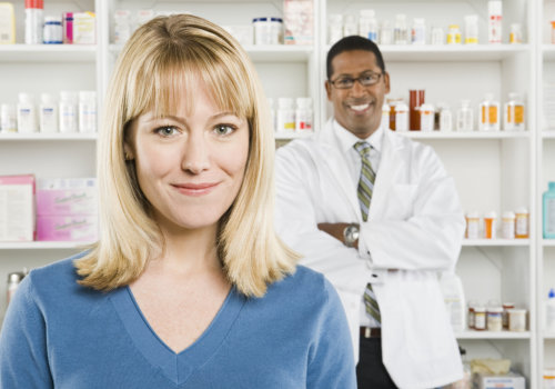 woman smiling with pharmacist at her back