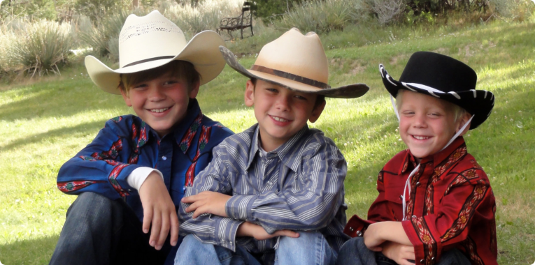 three boys in a cowboy outfit