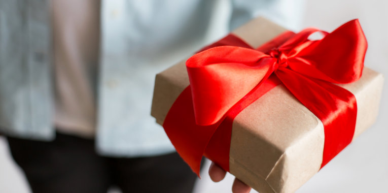 giving present with craft paper box and red ribbon